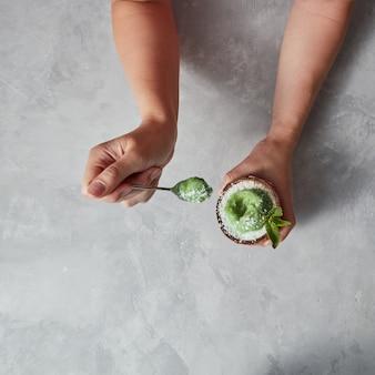 Heerlijk groen dessert, ijs in een kokosnoot in de hand van de vrouw met lepel op een grijze betonnen tafel met kopie ruimte. bovenaanzicht.