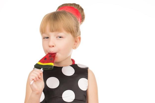 Heerlijk. horizontaal schot van een kleine cutie die watermeloenlolly eet