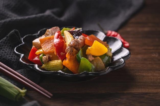 Heerlijk huisgemaakt roergebakken gezouten varkensvlees met kleurrijke paprika, babymaïs, wortel en houtoorzwam.