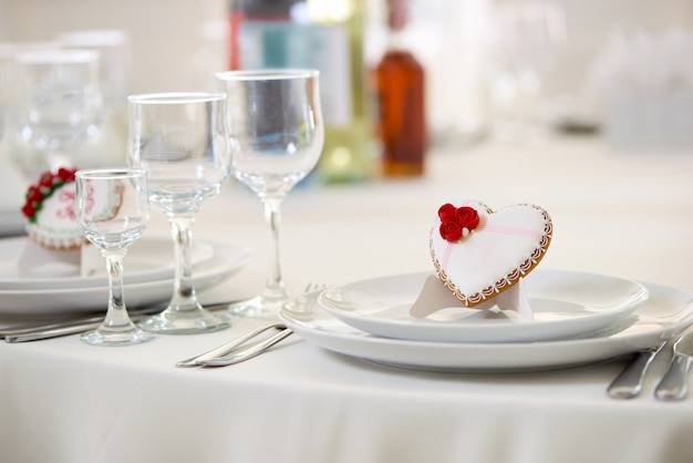 Heerlijk koekje bedekt met wit zoet glazuur en versierd met kleine rode rozen en witte kleine pareltjes staat op tafel, geserveerd met wijnglazen. goede decoratie voor voor een feestelijke bruiloftstafel.