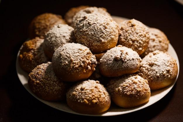 Heerlijk met knapperige broodjes, bestrooid met poedersuiker op een wit bord op bruin tafellaken