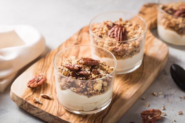 Heerlijk natuurlijk yoghurtparfait met karamel, pecannootnoten op conctere achtergrond