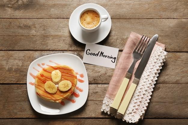 Heerlijk ontbijt en goedemorgen begroeting op houten tafel, bovenaanzicht