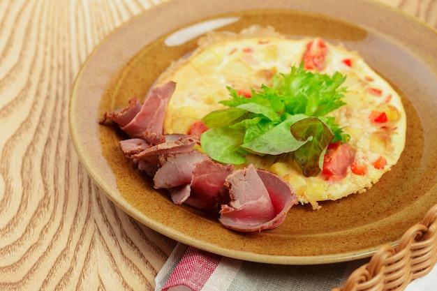 Heerlijk ontbijt gebraden omlette met gesneden ham dicht omhoog