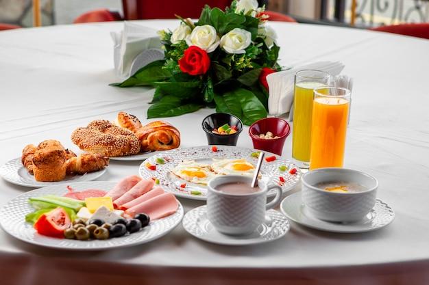 Heerlijk ontbijt in een tabel met salade, gebakken eieren en gebak zijaanzicht op een witte achtergrond
