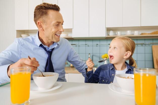 Heerlijk ontbijt. leuk positief jong meisje dat een lepel houdt en haar vader bekijkt tijdens het eten van ontbijt
