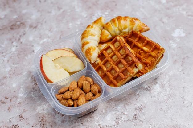 Heerlijk ontbijt met amandelen, rode appelschijfjes, wafels, croissants op plastic lunchbox op licht