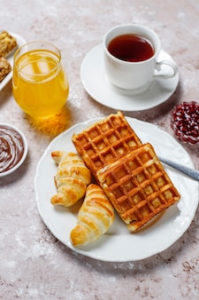 Heerlijk ontbijt met koffie, jus d'orange, wafels, croissants, jam, notenpasta op licht, bovenaanzicht