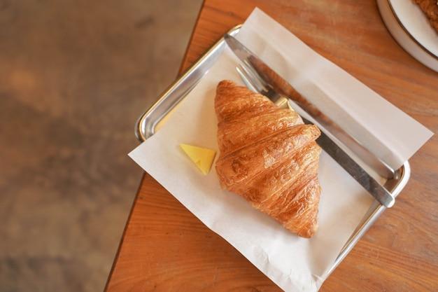 Heerlijk ontbijt met verse croissants en koffie geserveerd met boter op houten tafel.