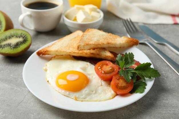 Heerlijk ontbijt of lunch met gebakken eieren op grijze ondergrond, close-up