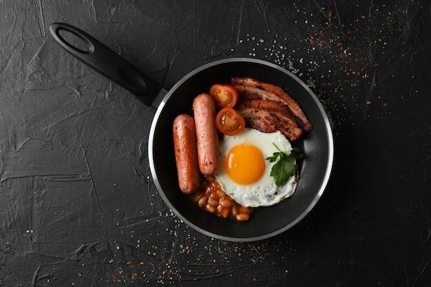 Heerlijk ontbijt of lunch met gebakken eieren op zwarte ondergrond, bovenaanzicht