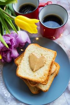 Heerlijk ontbijt op bed. zwarte koffie, felle bloemen, toast met pindakaas. detailopname.