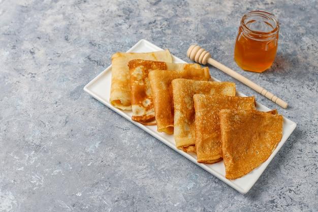 Heerlijk ontbijt. orthodoxe vakantie maslenitsa. pannenkoeken met cumquats en honet, bovenaanzicht