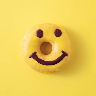 Heerlijk ontbijt vrolijke donut op een pastelgele achtergrond. minimaal trending concept