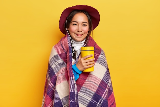 Heerlijk ontspannen vrouwelijke reiziger drinkt warme drank uit thermos, staat verpakt in plaid, geniet van wandeltocht, draagt hoed, vormt op gele achtergrond.