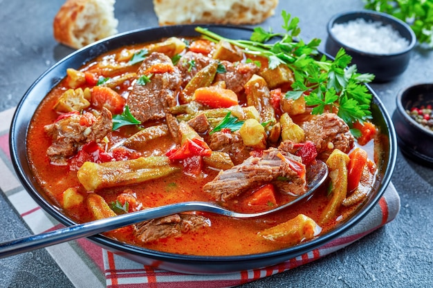 Heerlijk rundvlees en okra stoofpot of soep geserveerd in een kom met lepel, op een grijze betonnen tafel met ciabattabrood, uitzicht van bovenaf, close-up