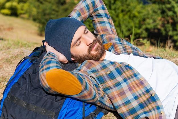 Heerlijk slapen. knappe jonge man liggend op de rugzak en hand in hand achter het hoofd