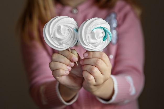 Heerlijk snoep op een stok in de handen van kinderen. het concept van snoep, feest, bakkerij.