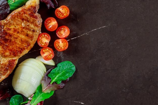 Heerlijk varkensvleeslapje vlees op steenachtergrond, close-up