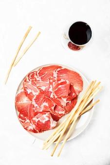 Heerlijk voorgerecht met broodstengels en ham, selectieve aandacht en bovenaanzicht