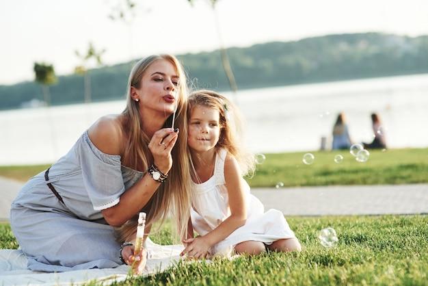 Heerlijk weer voor een vermaak. foto van jonge moeder en haar dochter die goede tijd hebben op het groene gras met meer bij achtergrond.