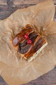 Heerlijk zoet gebakje met chocolade bij het koken van blad op houten oppervlakte.