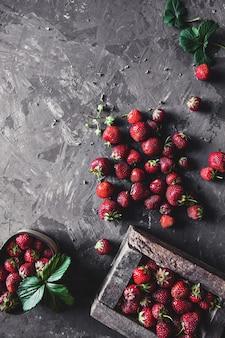 Heerlijke aardbeien met gele bloemen op een donkergrijze achtergrond in een vintage krans. gezond eten, fruit