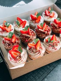 Heerlijke aardbeiendesserts op witte dozen en keukendoeken