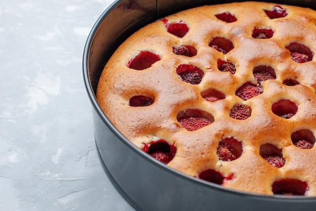 Heerlijke aardbeientaart gebakken met verse rode aardbeien binnen met pan op licht, cake koekjes fruit zoet deeg bakken