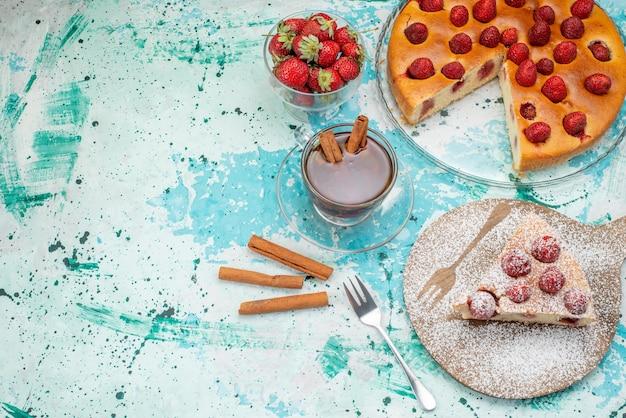 Heerlijke aardbeientaart in plakjes gesneden en hele heerlijke cake suiker gepoederd met thee op helderblauwe, bessentaart zoet gebakken deeg thee