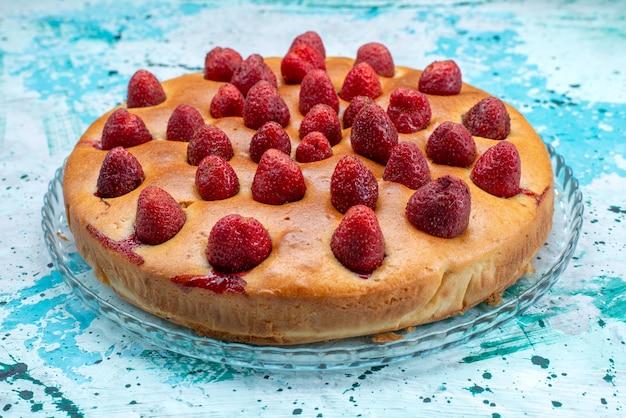 Heerlijke aardbeientaart rond gevormd met fruit bovenop helderblauwe, cakedeeg zoete koekjessuiker