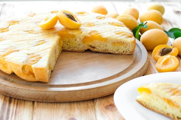 Heerlijke abrikozentaart op een houten bord met abrikozenvruchten op de achtergrond eenvoudig recept voor zomercake
