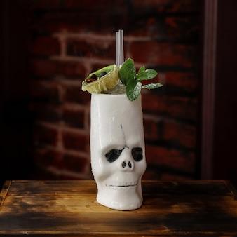 Heerlijke alcoholische cocktail met munt in een schedel-mok op een donkere muur