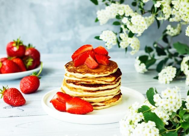 Heerlijke amerikaanse pannenkoeken met zoete aardbeien ontbijttijd concept