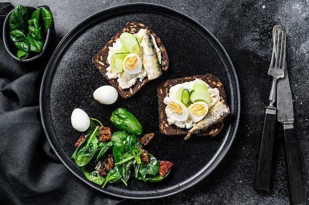 Heerlijke amuse tapas, zachtgekookte eieren en sandwiches met sardientjes uit blik.