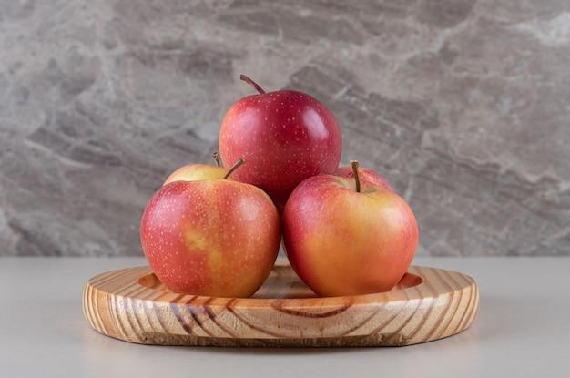 Heerlijke appels gebundeld op een schotel op marmer