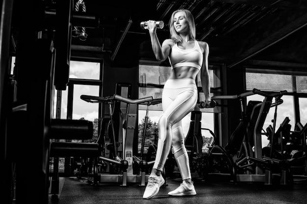Heerlijke atleet poseren in de studio met gewichten in haar handen. het concept van sport, bodybuilding, sportvoeding. gemengde media