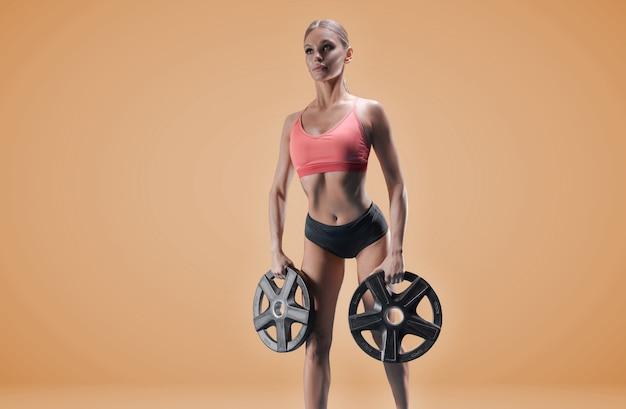 Heerlijke atleet poseren in de studio met gewichten in haar handen. het concept van sport, bodybuilding, sportvoeding.