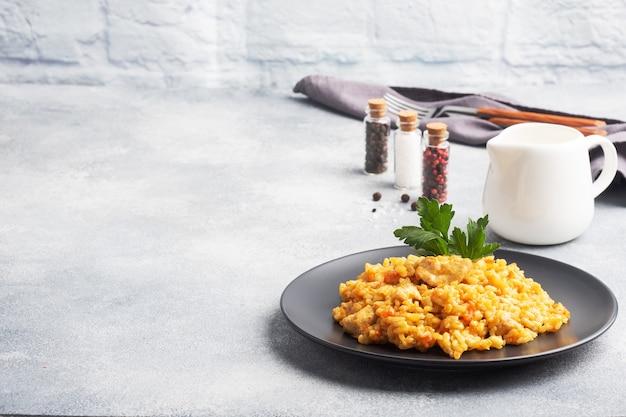 Heerlijke aziatische pilaf, gestoofde rijst met groenten en kip op een bord. grijze betonnen achtergrond. ruimte kopiëren.