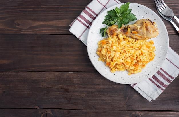 Heerlijke aziatische pilaf, gestoofde rijst met groenten en kippentrommelstok op een plaat. houten rustiek. bovenaanzicht