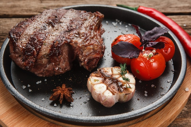Heerlijke beafstaak geserveerd met gegrilde tomaten en knoflook en versierd met basilicum en chili, close-up uitzicht.