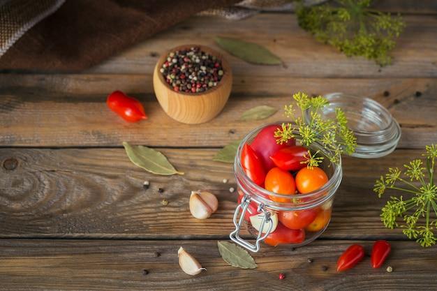 Heerlijke, biologische, smakelijke en rijpe tomaten met kruiden en knoflook in glazen pot