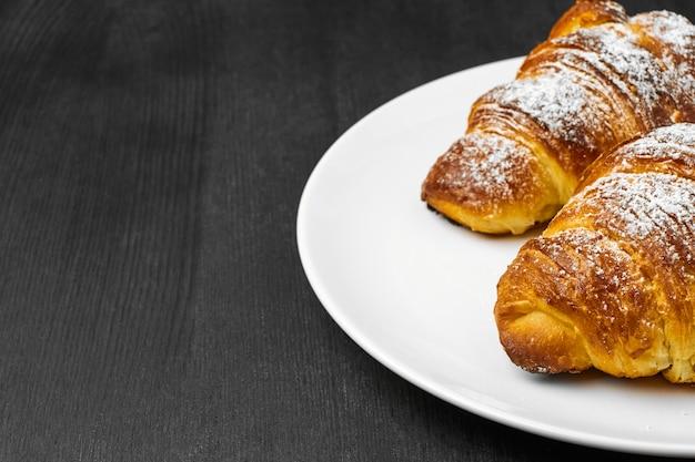 Heerlijke boterachtige croissants op een witte plaat op een zwarte houten achtergrond met exemplaarruimte.