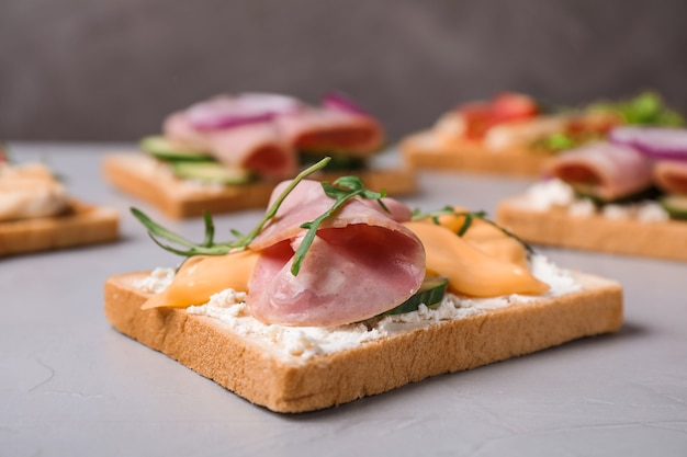 Heerlijke broodjes met ham op grijze tafel, close-up
