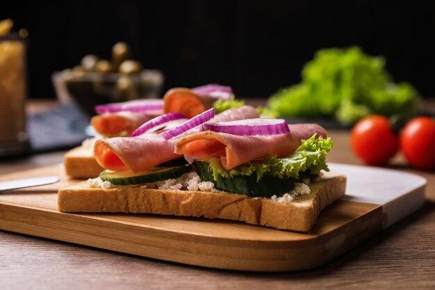 Heerlijke broodjes met ham op houten tafel, close-up