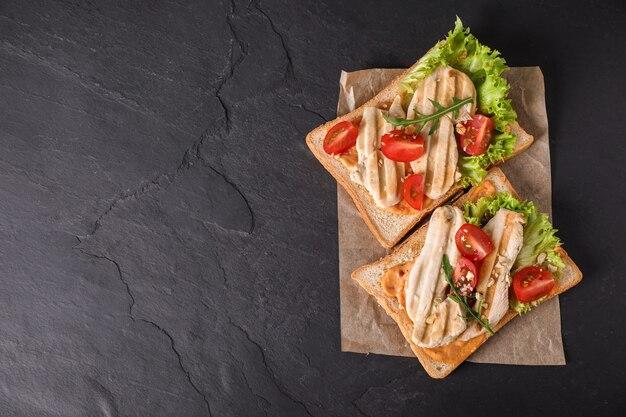 Heerlijke broodjes op zwarte tafel, bovenaanzicht. ruimte voor tekst