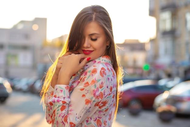 Heerlijke brunette vrouw die blouse draagt, die zich voordeed op de achtergrond van de avondstad