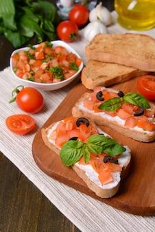Heerlijke bruschetta met tomaten op snijplank close-up