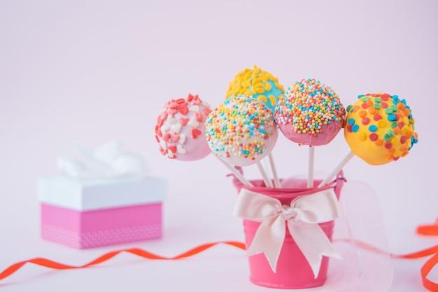 Heerlijke cake en een cadeau op een roze achtergrond, naast een rood en roze lint.