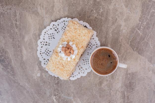 Heerlijke cake en kopje koffie op marmeren oppervlak.
